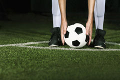Athlete placing soccer ball for corner kick at night Royalty Free Stock Image