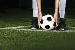 Athlete placing soccer ball for corner kick at night Royalty Free Stock Image
