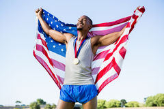 Athlete posing with american flag and gold medals around his neck Royalty Free Stock Photos