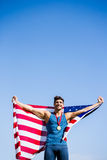 Athlete posing with american flag and gold medals around his neck Royalty Free Stock Photo