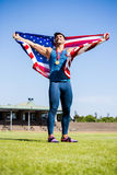 Athlete posing with american flag and gold medals around his neck Stock Photography