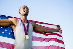 Athlete posing with american flag and gold medals around his neck Royalty Free Stock Photography