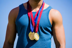 Athlete posing with gold medals around his neck Stock Photo