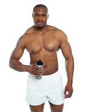 Athlete posing with health drink bottle Royalty Free Stock Images