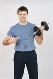 Athlete with a positive indicates dumbbell Stock Photo