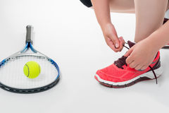 Athlete preparing for the match in tennis, tying lace on a white Stock Photo