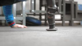 The athlete with a prosthetic arm is pushing out. Does exercise on the floor while lying. Professional prosthetic arm