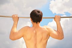 Athlete pull oneself up on sky background Royalty Free Stock Photos