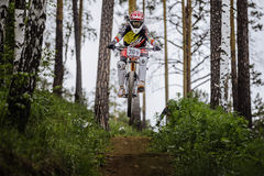 Athlete racer bike jump with a mountain in forest on helmet video camera Stock Photo