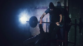 The athlete raises the bar lying in the gym stock video