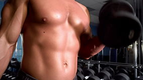 Athlete raises two dumbbells at the gym. Near the mirror stock footage