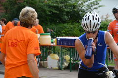 Athlete receives energy drink at a triathlon event Stock Photography