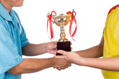 Athlete receiving gold trophy during prize presentation ceremony. On white background stock images