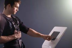 Athlete regulating intensity of ems electro muscular stimulation machine Stock Photography