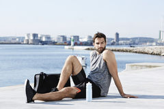 Athlete resting by sea. With view Stock Images