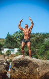 Athlete on a rock by the sea against the sky Royalty Free Stock Images