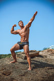 Athlete on a rock by the sea against the sky Stock Photos