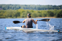 Athlete rower on rowing kayak on lake Royalty Free Stock Images