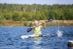 Athlete at rowing kayak on lake, spray of water under paddle Royalty Free Stock Photography