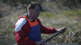 Rear view of Athlete rowing on the river in a canoe. Rowing, canoeing, paddling. Training. Kayaking. Man sailing against. Athlete rowing on the river in a canoe stock video footage