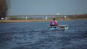 Rear view of Athlete rowing on the river in a canoe. Rowing, canoeing, paddling. Training. Kayaking. Man sailing against. Athlete rowing on the river in a canoe stock video