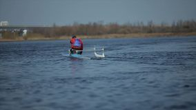 Rear view of Athlete rowing on the river in a canoe. Rowing, canoeing, paddling. Training. Kayaking. Man sailing against. Athlete rowing on the river in a canoe stock footage