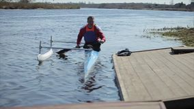 Athlete rowing on the river in a canoe. Man approaching the pier. Rowing, canoeing, paddling. Training. Kayaking. Man. Sailing against the bridge. Sunny day stock footage