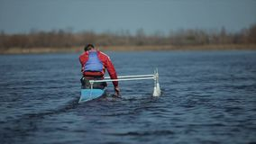 Rear view of Athlete rowing on the river in a canoe. Rowing, canoeing, paddling. Training. Kayaking. Athlete rowing on the river in a canoe. Rowing, canoeing stock video footage