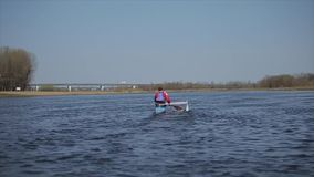 Rear wide view of Athlete rowing on the river in a canoe. Rowing, canoeing, paddling. Training. Kayaking. Man sailing. Athlete rowing on the river in a canoe stock video