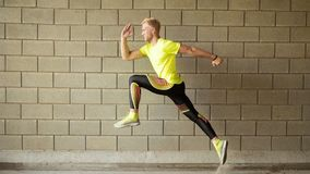 Running young man, gray wall on background stock image