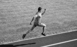 Athlete run track grass background. Sprinter training at stadium track. Runner captured in midair. Short distance. Running challenge. Boost speed. Run into stock photo