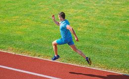 Athlete run track grass background. Sprinter training at stadium track. Runner captured in midair. Short distance. Running challenge. Boost speed. Run into royalty free stock photography