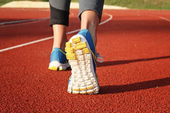 Athlete runner feet down stadium track. Closeup on female shoe and legs. Woman autumn  fitness workout. Jogging, sport, healthy ac Royalty Free Stock Image