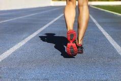 Athlete runner feet down stadium track Royalty Free Stock Photos