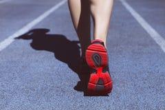 Athlete runner feet down stadium track. Closeup on female shoe a Royalty Free Stock Image