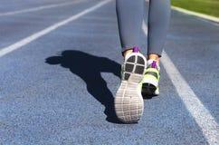 Athlete runner feet down stadium track. Jogging, sport, healthy Stock Photo