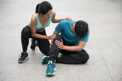Athlete runner hold his pain sprained ankle leg. Asian athlete sport male runner hurt and hold his painful sprained ankle while girlfriend check pain severity Royalty Free Stock Photos