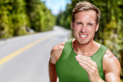 Athlete runner on intense cardio running workout. Athlete on intense cardio running workout. Closeup portrait of male sprinter or long distance runner in hard Stock Photography