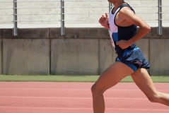 Athlete runner running on athletic track. Side view Stock Photo