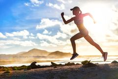 Athlete runner trail running on summer beach. Fit body silhouette of sports Woman in sportswear cap sprinting with energy and motion in outdoors nature stock image