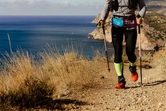Athlete runner with trekking poles. Running mountain trail along sea Stock Photos