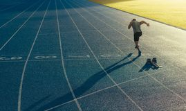 Sprinter running on track. Athlete running on an all-weather running track alone. Runner sprinting on a blue rubberized running track starting off using a Royalty Free Stock Photos
