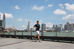 Athlete running along the waterfront Marina Bay in Singapore Royalty Free Stock Images