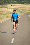 Athlete running in country road Royalty Free Stock Photo