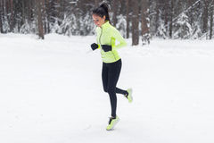 Athlete running fit woman Sporty girl jogging Winter park forest. Royalty Free Stock Photo