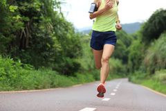 Athlete running on forest trail. woman fitness jogging workout wellness concept. Royalty Free Stock Image