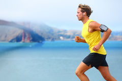 Athlete running man - male runner in San Francisco. Listening to music on smartphone. Sporty fit young man jogging by San Francisco Bay and Golden Gate Bridge Royalty Free Stock Image