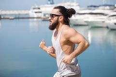 Athlete running man - male runner by the sea pier with yachts. Athlete running man - male runner in San Francisco listening to music on smartphone. Sporty fit Stock Image
