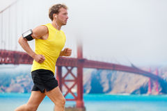 Athlete running man runner - San Francisco living. Athlete running man - male runner in San Francisco listening to music on smartphone. Sporty fit young man Royalty Free Stock Image