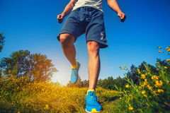 Athlete running through the meadow. stock photography
